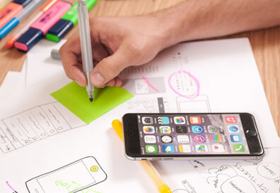 close up of someone sketching mobile wireframes